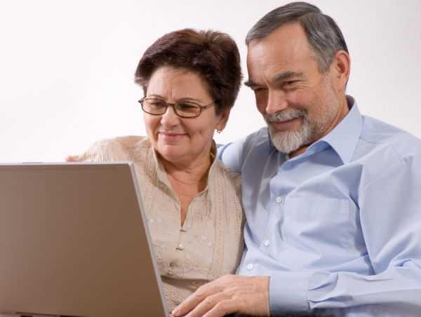 Az akadálymentesség üzenete: Egy idős házaspár egy laptopot néz otthon. Ők is könnyen tudják használni, ami akadálymentes.