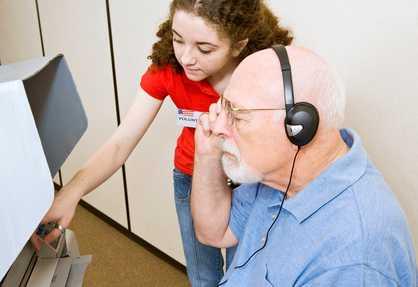 Illusztráció: egy fiatal magyarázza egy látássérült férfinak az érintőképernyős szavazórendszer használatát.