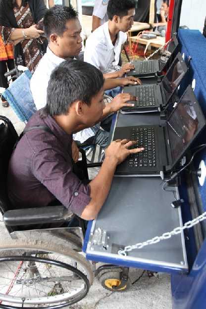 Tolószékes, egy kezét használni tudó fiatalember internetezik egér nélkül