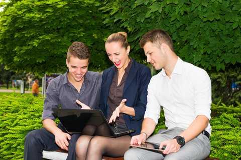Illusztráció: egy fiatalember, egy férfi és egy nő nézik a laptopot egy kerti padon. Az internetezés öröm mindenkinek.