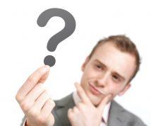 Egy ember egy kérdőjelet nézeget. A kérdőjel a kép középpontja.