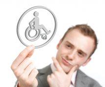 Egy férfi egy fogyatékosságot jelentő ikont (kerekesszék) tart a kezében, ujjaival az állát fogja, töpreng a jelentésén. Mit jelent az akadálymentesség?